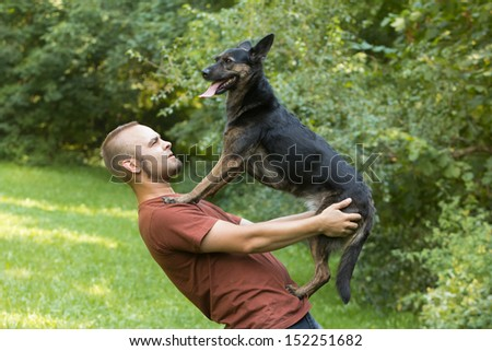 A young man practicing tricks with dog - stock photo