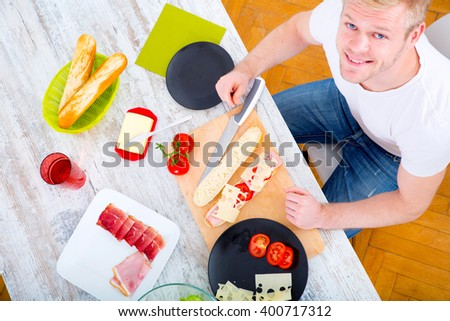 A young man preparing a sandwich in the kitchen. - stock photo