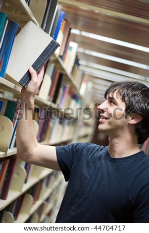 A young man pulling a book from the shelf at the library. - stock photo