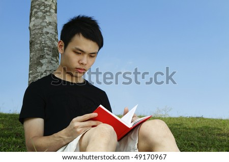 A young man reading a book while leaning on a tree outdoors - stock photo