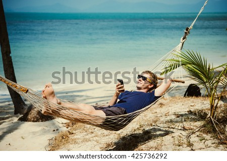 A young man relaxes in a hammock at the beach while checking messages on his smartphone. Toned image - stock photo