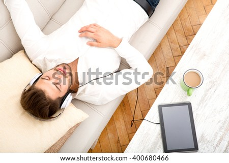 A young man relaxing and listening to music on the couch.