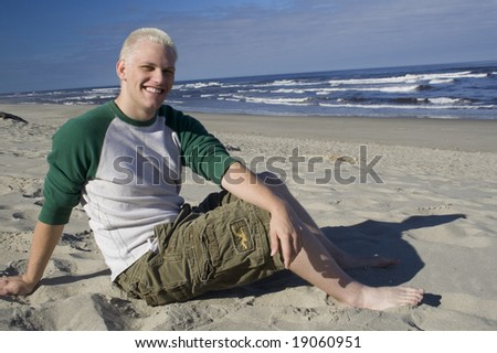 A young man relaxing on the sandy beach in the morning