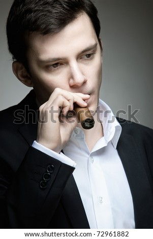 A young man relaxing with a cigar - stock photo