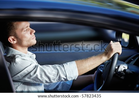 A young man rides in a car at high speed - stock photo