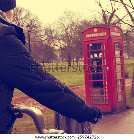 a young man riding a bicycle in Hyde Park in winter in London, United Kingdom, with a typical red telephone booth in the background - stock photo