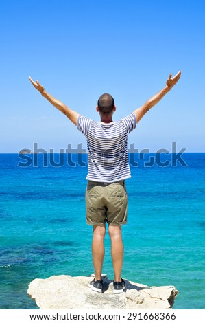 a young man, seen from behind, with his arms in the air in front of the ocean, feeling free - stock photo
