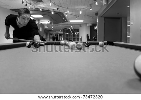 A young man shooting pool with motion blur on the pool balls. Shallow depth of field. - stock photo
