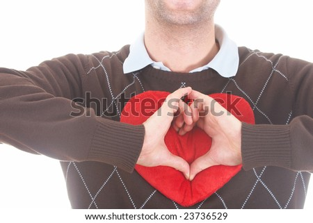 A young man shows a heart shape with his hands on a red heart-shaped pillow. Isolated over white. - stock photo