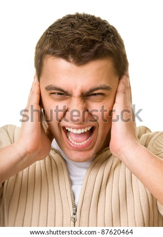 A young man shuts his ears hands - stock photo
