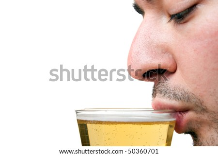 A young man sipping a tall glass of beer isolated over white.  Shallow depth of field with sharp focus on the lip and beer. - stock photo
