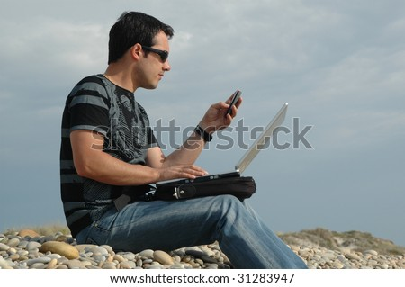 a young man sited on the beach working with a laptop and with mobile phone