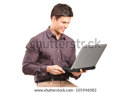 A young man sitiing on a high chair and working on a laptop isolated on white background