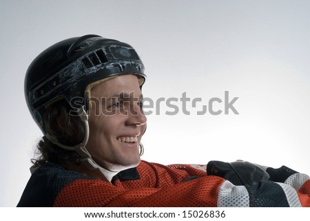 A young man, sits on the floor, smiling happily, while he wears a full ice hockey uniform. Horizontally framed shot. - stock photo