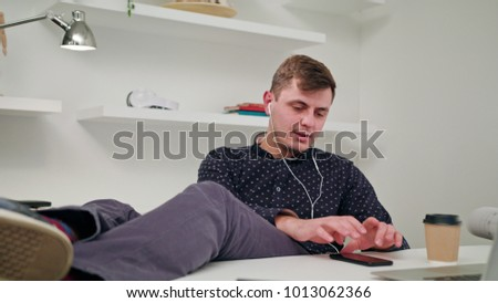 A young man sitting and listening to music indoors. Medium Dolly shot.