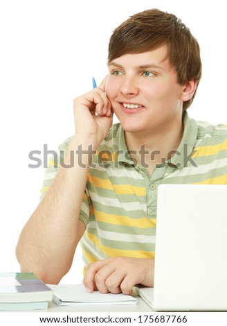 A young man sitting in front of a laptop, isolated on white - stock photo