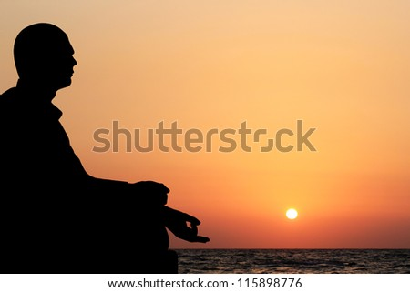 A young man sitting in lotus position and meditating on a beach in the evening with sun setting in the background. The sky is orange yellow and the ocean can also be seen in the meditation backdrop - stock photo
