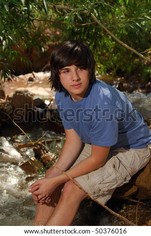 A young man sitting on a rock in a mountain stream