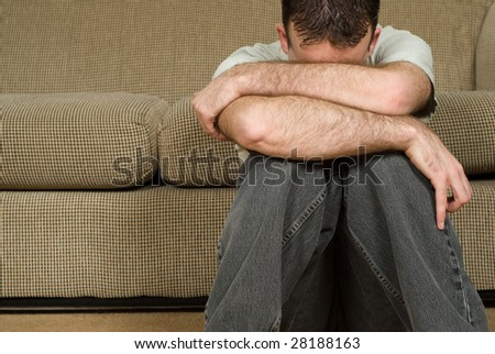 A young man sitting on the floor suffering from clinical depression - stock photo