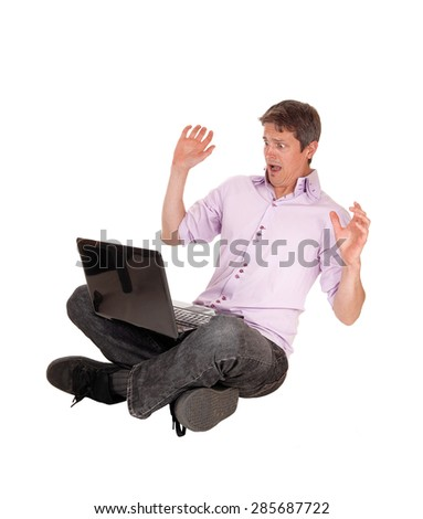 A young man, sitting on the floor with his laptop on his lap and isscared what he see's on the laptop isolated foe white background. - stock photo