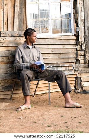 A young man sitting outdoors in a township on a steel chair with a text book in his hands - stock photo