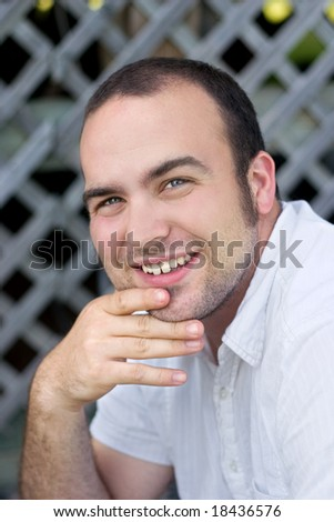 a young man smiling into the camera - stock photo