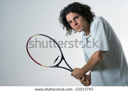 A young man, standing, holds a tennis racket as if he is about to hit a ball. Horizontally framed shot. - stock photo