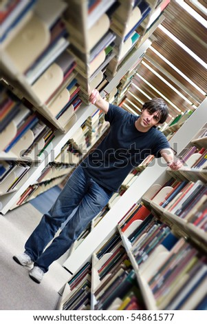 A young man standing in the aisles of the library book shelves. - stock photo