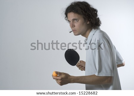 A young man, stands holding a ping pong paddle and ball, staring intently, preparing to serve. Horizontally framed shot. - stock photo