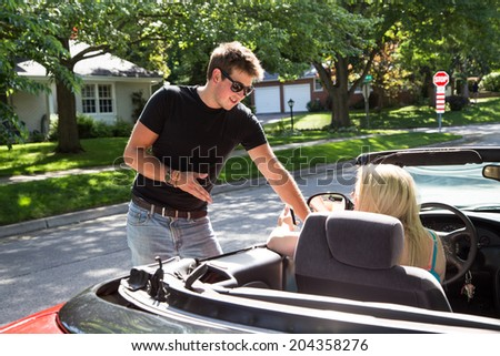 A young man stands talking to a young lady in a red convertible.  He may be giving her directions or perhaps asking her out. - stock photo