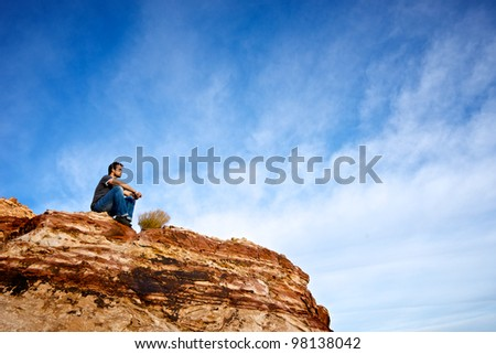 A young man stares out across the Red Rock State Park outside Las Vegas, Nevada, - stock photo