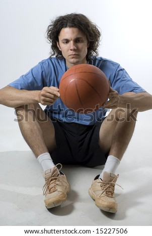 A young man, staring at a basketball in his hands, sits wearing a tee-shirt and shorts. Vertically framed shot. - stock photo