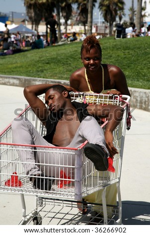 a young man suffers from too much partying is pushed home in a grocery cart by his friends - stock photo