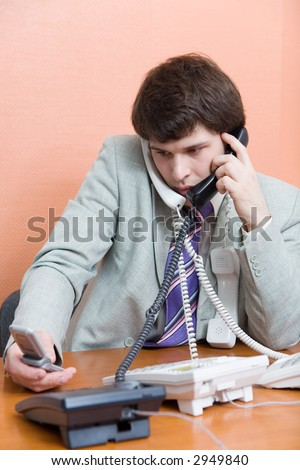 A young man talking on the phones at office