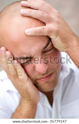 A young man that looks to be losing his mind and grabbing his head in desperation. - stock photo