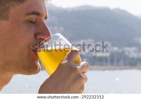 A young man tries to beer in the early morning on the beach