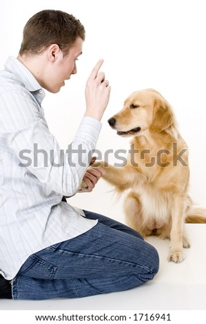 A young man tries to train his pet dog to shake hands/paws