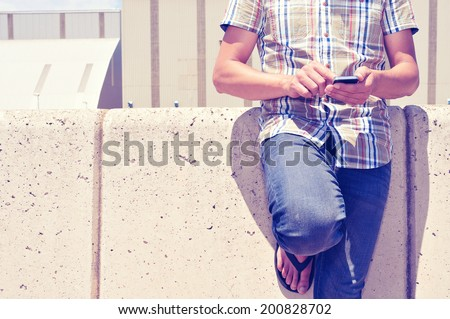 a young man using a smartphone outdoors - stock photo