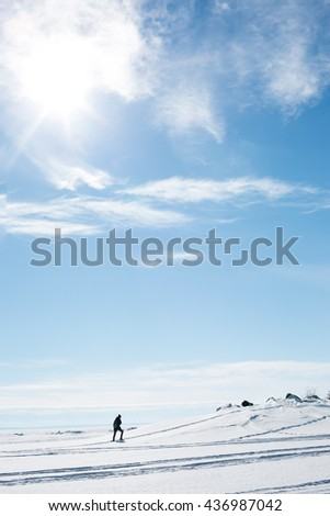 A young man walks alone in the snowy wilderness. - stock photo