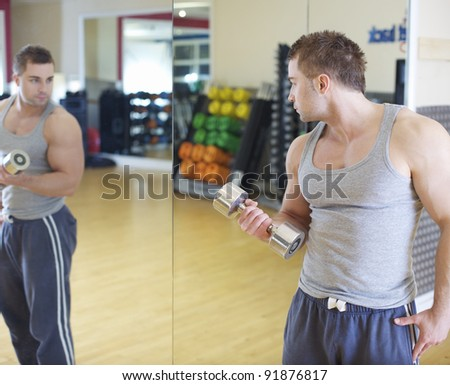 A young man watches in the mirror as he performs a bicep curl with a chrome dumbbell - stock photo