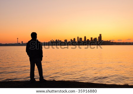 A young man watching the sun rise behing the Seattle skyline across the bay - stock photo