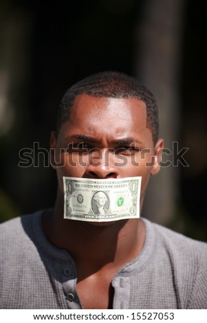 a young man wears a dollar bill taped over his mouth in protest against inflation and the rising cost of goods and services - stock photo