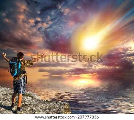 A young man with a backpack looks like a huge fiery meteorite falls into the sea - stock photo