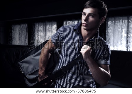 a young man with a bag - stock photo