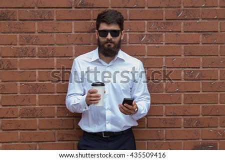 a young man with a beard against the backdrop of a brick wall with coffee in hand and glasses - stock photo
