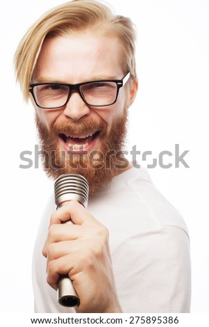 A young man with a beard wearing a shirt holding a microphone and singing, hipsterstyle. Over white background. - stock photo