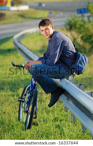 A young man with a bicycle on the highway