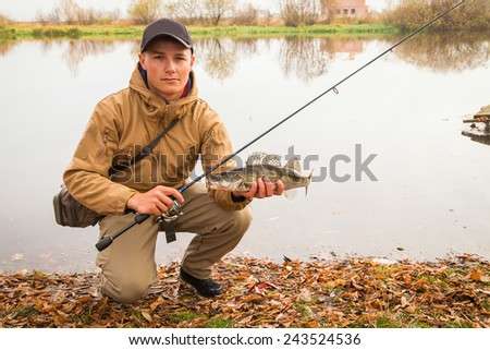 A young man with a fish in his hands and spinning. A fisherman on the river caught zander. Man fisherman sat on his legs and holding a fish in his hands.