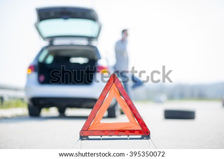 A young man with a silver car that broke down on the road.He has set up a warning triangle.He is waiting for the technician to arrive. - stock photo
