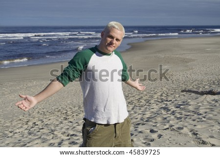 A young man with arms outstretched on the beach in the morning - stock photo